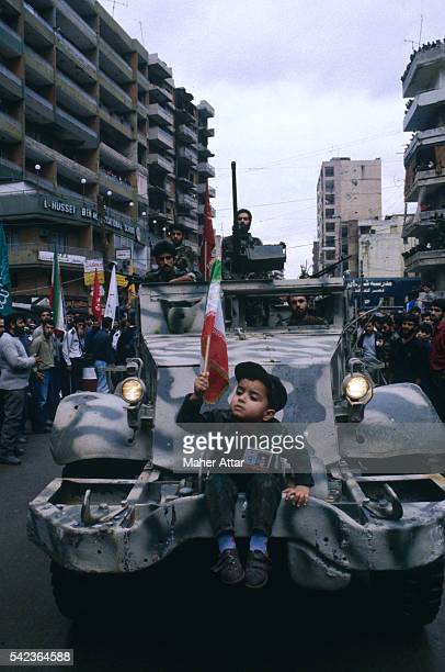 A child sitting on an armored car holds up a flag at a Hezbollah rally in a southern suburb of Beirut