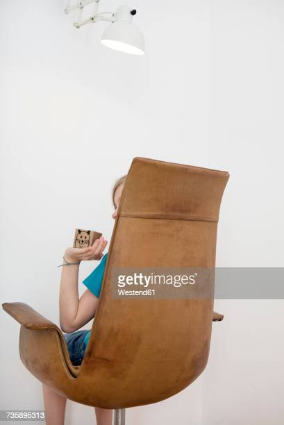 Child sitting on armchair holding box with painted mouse
