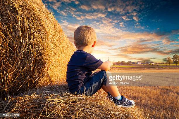 Child sitting on bales of straw