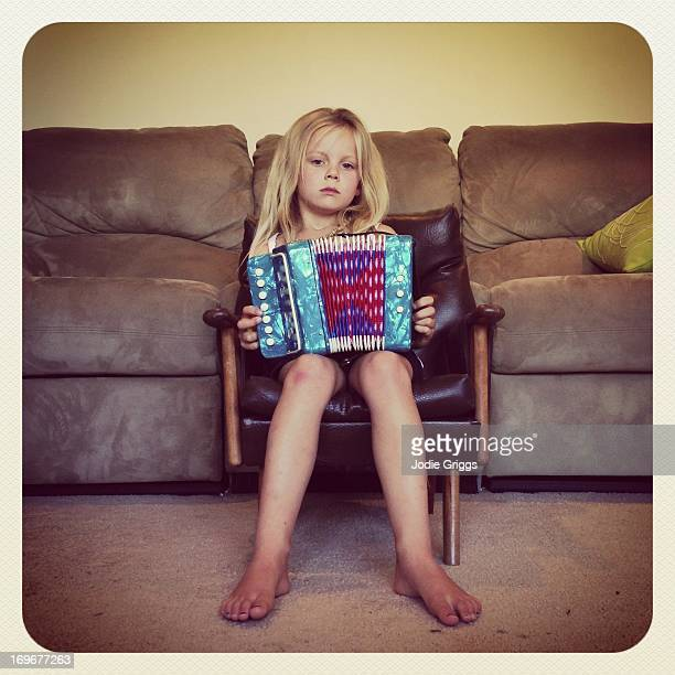 Child sitting on chair playing small accordion