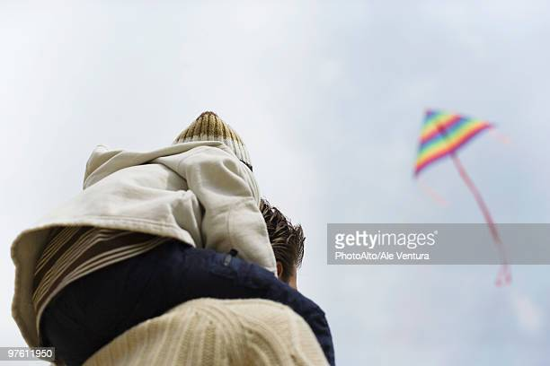 Child sitting on father's shoulders, looking at kite in sky