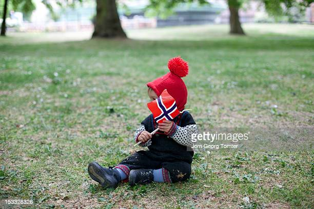child sitting on grass holding norwegian flag - norwegian flag stock pictures, royalty-free photos & images