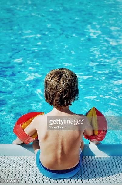 Enfant assis sur le bord de la piscine