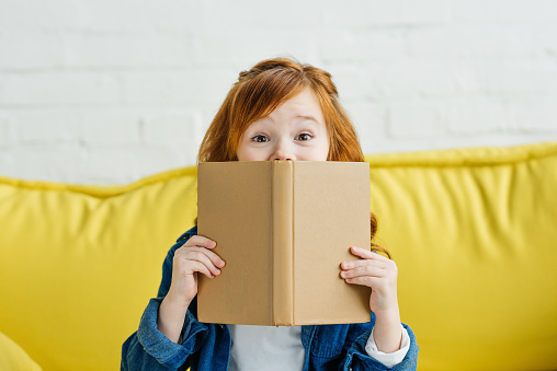 Child sitting on sofa and holding book in front of her face 993795898