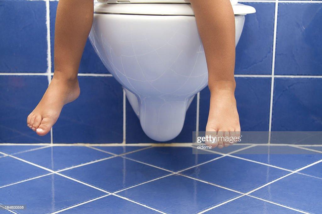 Child sitting on the toilet : Stock Photo