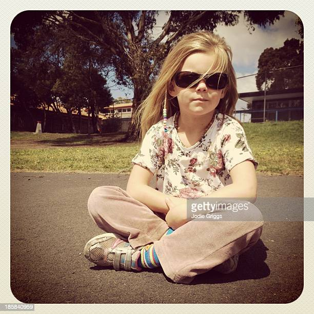 Child sitting outside wearing sun glasses