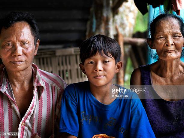 A child sitting with his family in rural Malaysia.