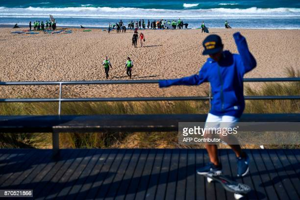 A child skateboards past Web Summit attendees taking part in a surf lesson at Foz do Lizandro beach in Ericeira on November 5 2017 during a 2017 Web...