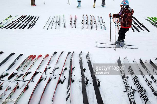 A child skier passes skis placed on snow at the Niseko Hanazono resort operated by Nihon Harmony Resorts KK in Kutchan Hokkaido Japan on Sunday Feb...