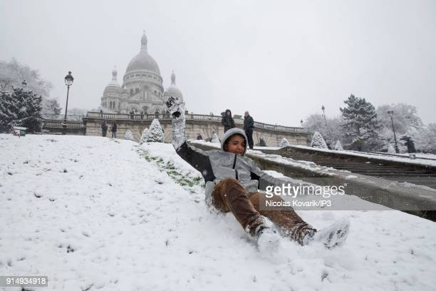 A child sledges on Montmartre hill near the Sacre Coeur during a snowfall on February 6 2018 in Paris France Several french departments are affected...