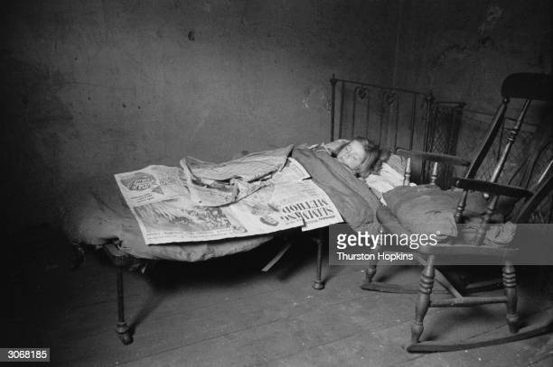A child sleeping in a slum dwelling in the backstreets of Liverpool where 88000 of the houses are deemed unfit for human habitation Original...