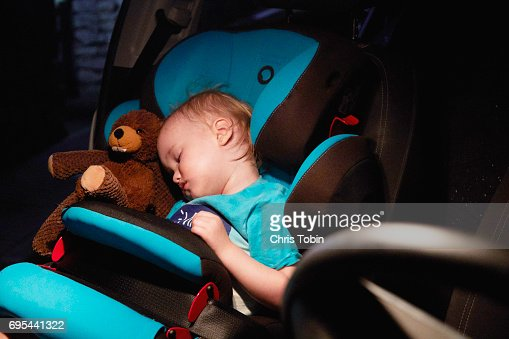Child sleeping in car seat with stuffed animal