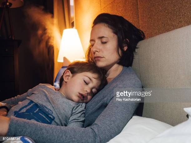 child sleeping in mothers arms - krankheit stock-fotos und bilder