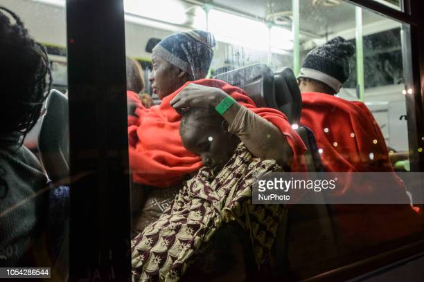 A child sleeping in the arms his her mum inside of the bus to be transferred to a center Malaga