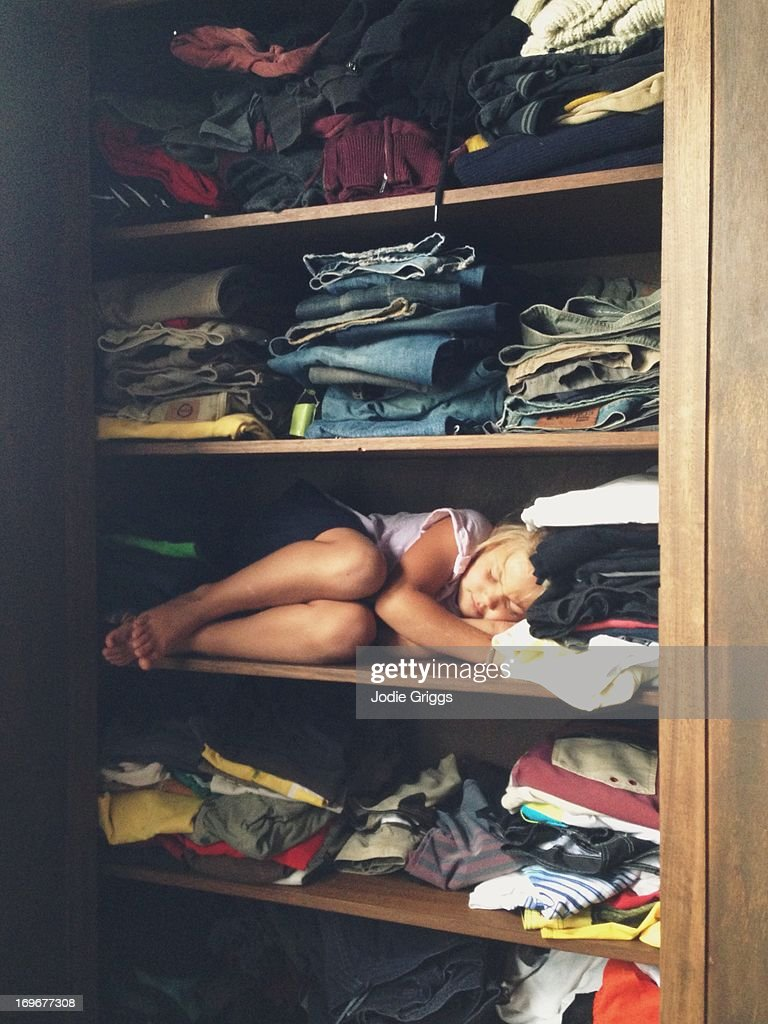 Child sleeping on shelf in clothes cupboard : Stock Photo