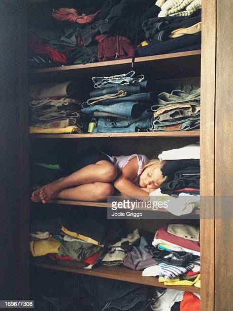 child sleeping on shelf in clothes cupboard - dormir humour photos et images de collection