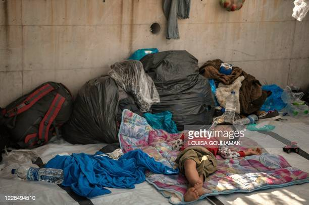 Child sleeps along the roadside where thousands are living with out shelter and exposed to the elements following the burning down of their camp,...
