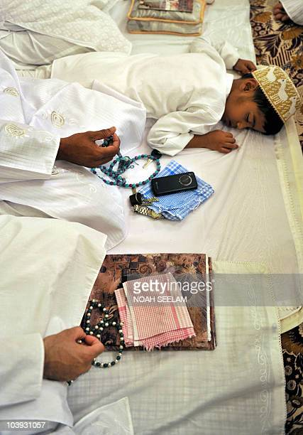 A child sleeps as Indian Bohra Muslims offer Eid prayers at the Fatemi Mosque in Hyderabad early on September 9 2010 Bohras adhere to the Shia Fatimi...