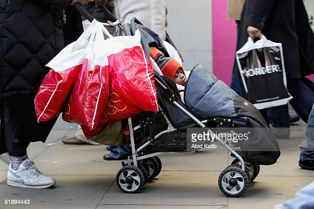 A child sleeps in it's heavily bag laden buggy on Oxford St on December 26 2004 in London England Thousands to to the streets of the capital to take...