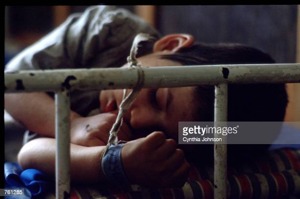 A child sleeps with his hand tied to the bars at an orphanage May 16 1990 in Ploiesti Romania The orphanage is for children who have birth defects...