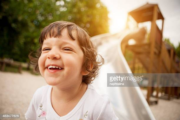 Child smiling after slide at park