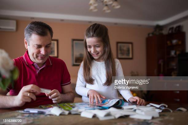 child smiling when filling in uefa sticker album with her father - final game stock pictures, royalty-free photos & images