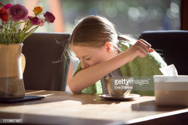 child sneezing into elbow and sitting at a table near to a bunch of flowers in a vase - real body fotografías e imágenes de stock