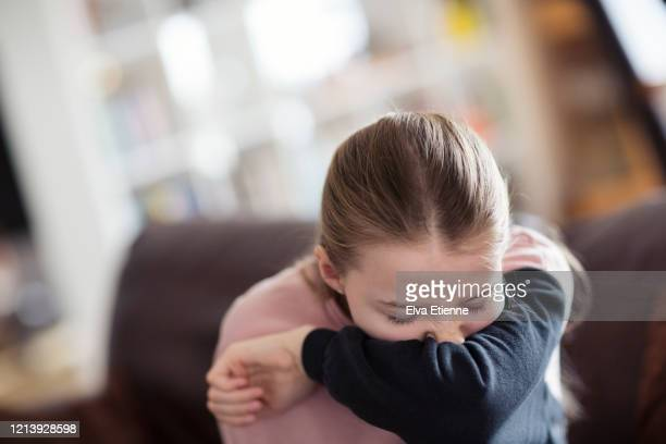 child sneezing into elbow - cold and flu stock pictures, royalty-free photos & images