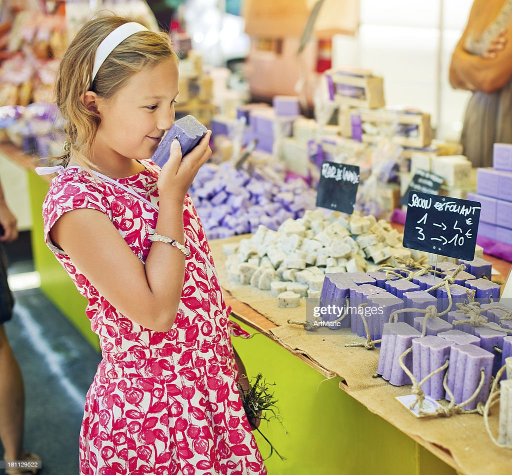 Child sniffing soap at a farmer's market in Provenve : Stock Photo
