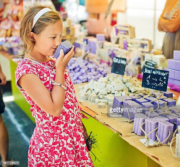 Child sniffing soap at a farmer's market in Provenve