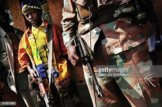 A child soldier from the Mai Mai stands close to a UN South African peacekeeper 04 December 2004 in Mutongo a village in the Walikale district during...