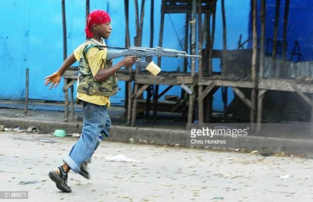 A child soldier loyal to the government fires off a volley of automatic weapons fire July 23 2003 in Monrovia Liberia Clashes continuted in the...
