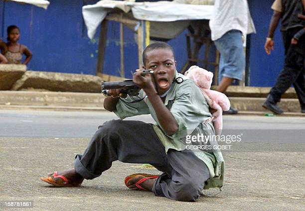 A child soldier wearing a teddy bear backpack points his gun at a photographer in a street of Monrovia 27 June 2003 where Liberian President Charles...