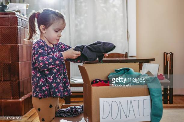 child sorting clothes for donation - selfless stock pictures, royalty-free photos & images