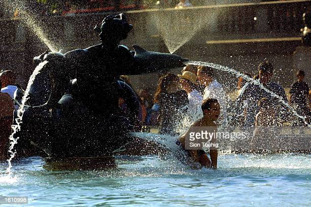 A child splashes in a fountain August 27 2001 in Trafalgar Square London