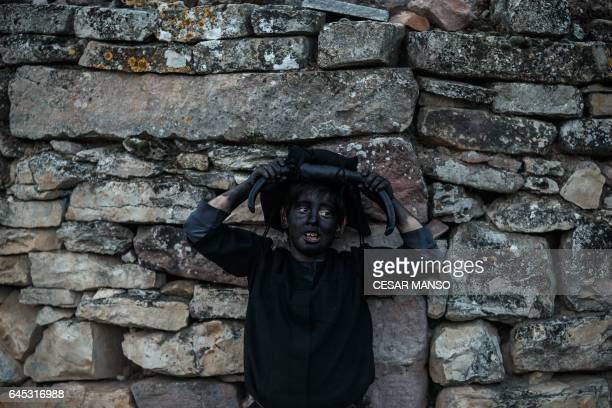 A child sporting horns on his head and grease on his face to represent 'Diablos de Luzon' poses during the carnival in Luzon near Guadalajara on...