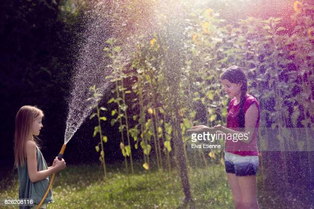 Child spraying water from garden hose onto a teenager