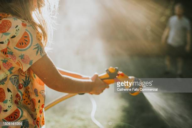 a child sprays a garden hose - human limb stock pictures, royalty-free photos & images
