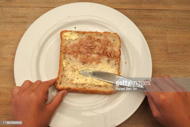 child spreading margarine on slice of bread - rafael ben ari stock pictures, royalty-free photos & images