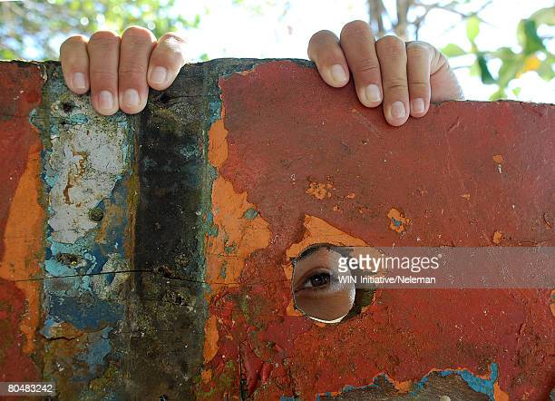 child spying behind rusted wall - peeping holes ストックフォトと画像