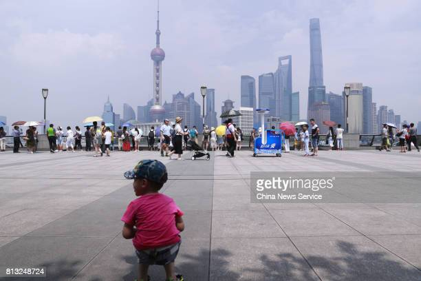 A child squats in the shade at The Bund on July 12 2017 in Shanghai China The dog days of summer start from July 12 in China Shanghai released on...