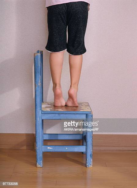 Child standing and reaching out on chair