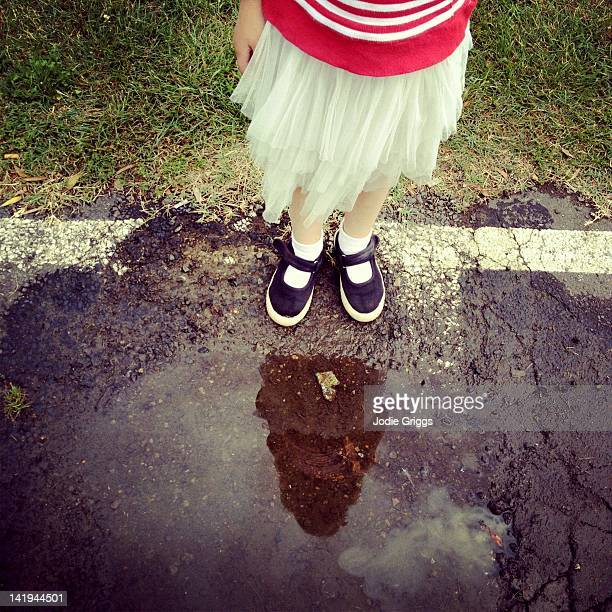 Child standing at edge of puddle