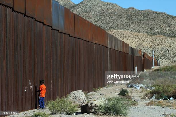 A child standing at the border wall observes the Not Walls demonstration by activists in the US in front of the wall that divides Ciudad Juarez...