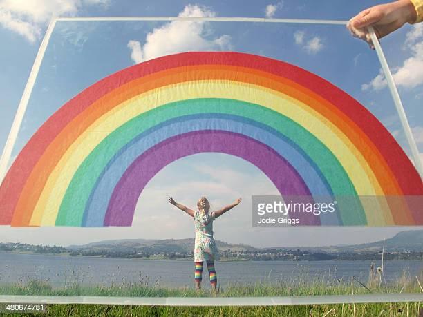Child standing beneath paper rainbow held by child