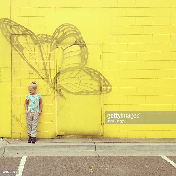 Child standing beside butterfly painted on wall