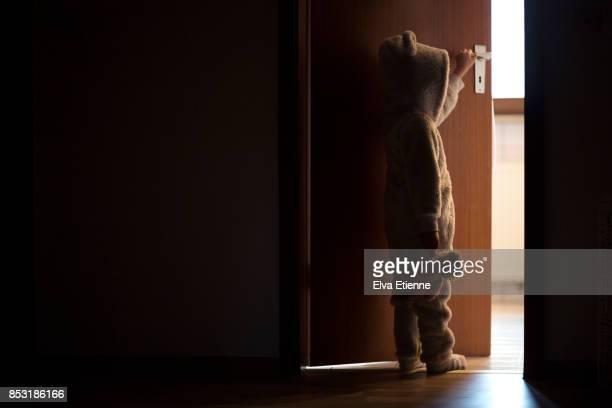 Child standing in a darkened doorway, opening a door to the light