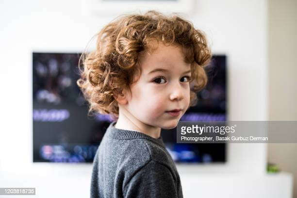 a child standing in front of tv, looking directly to the camera - 6 7 jahre stock-fotos und bilder