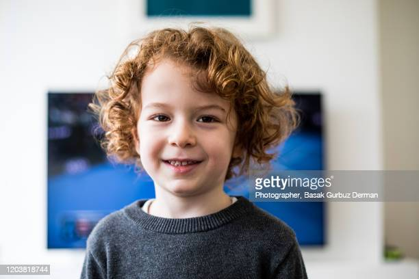 a child standing in front of tv, looking directly to the camera, smiling - one boy only stock pictures, royalty-free photos & images