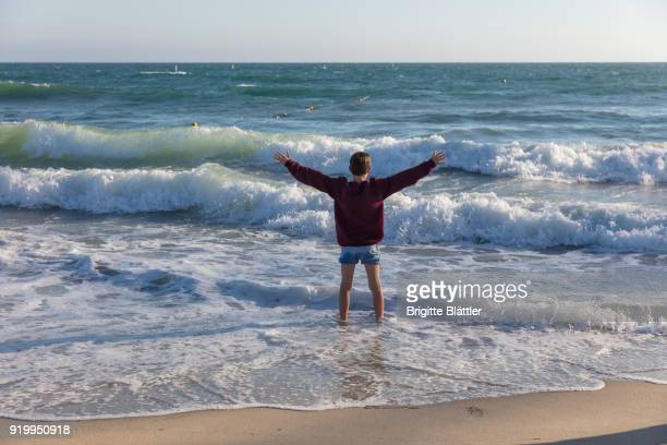 Child standing in pacific ocean